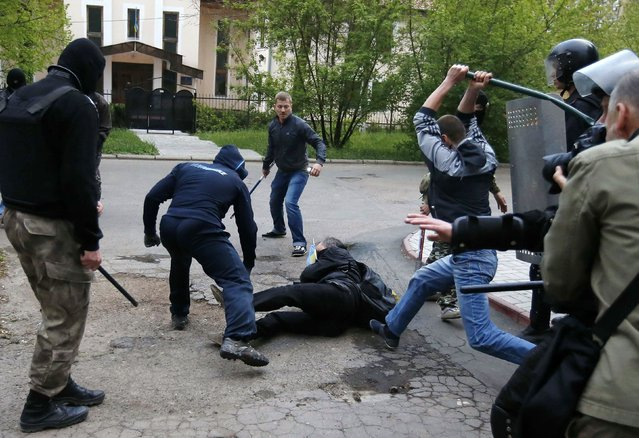 Pro-Russian protesters attack a pro-Ukrainian protester during a rally in the eastern city of Donetsk, on April 28, 2014. Several people were wounded when what appeared to be stun grenades exploded during a rally in support of Ukrainian unity in the eastern, separatist-held city of Donetsk, Reuters reported. (Photo by Marko Djurica/Reuters)