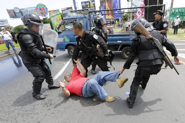 Riot policemen detain an opposition supporter during a protest in front of the Supreme Electoral Council (CSE) building in Managua, Nicaragua July 8, 2015. The protesters were demonstrating to demand for what they call fairer elections in the country next year. (Photo by Reuters/Stringer)