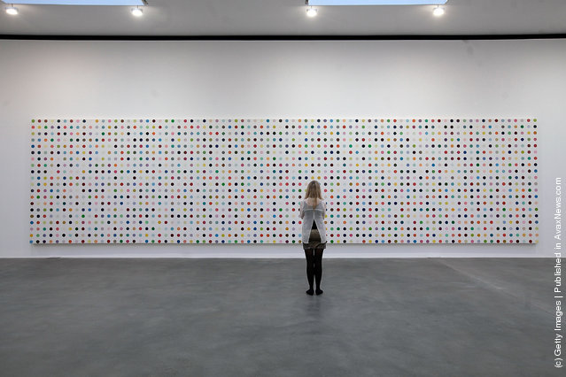 An employee looks at the artwork 'L-Tyrosince-15N, 2001', part of the artist Damien Hirst's exhibition The Complete Spot Paintings