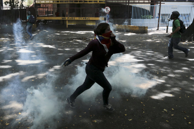 A demonstrator throws back a tear gas canister during clashes with security forces at a protest in Caracas, Venezuela, Wednesday, April 19, 2017. (Photo by Fernando Llano/AP Photo)