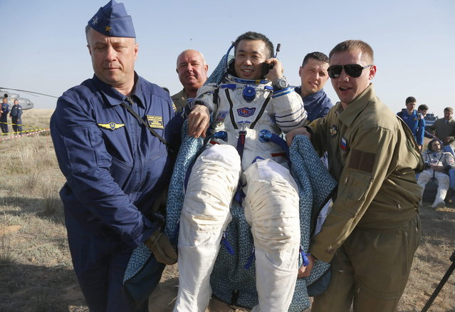 A Russian space agency rescue team members carries Japanese astronaut Koichi Wakata shortly after the landing of the Russian Soyuz TMA-11 space capsule about 150 kilometers (93 miles) southeast of the Kazakh town of Dzhezkazgan, Kazakhstan, Wednesday, May 14, 2014. The Soyuz space capsule with Wakata, Russian cosmonaut Mikhail Tyurin and U.S. astronaut Rick Mastracchio, returning from a half-year mission to the International Space Station landed safely Wednesday on the steppes of Kazakhstan. (Photo by Dmitry Lovetsky/AP Photo)