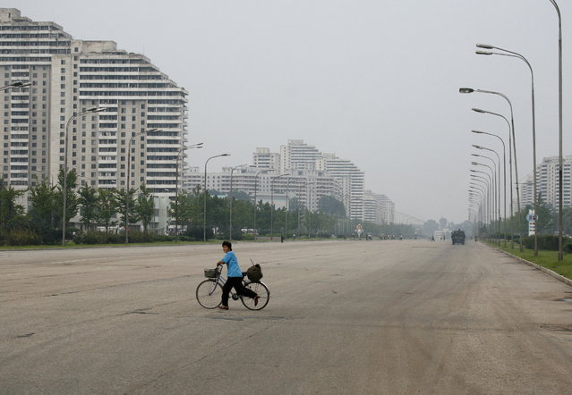 A North Korean woman pushes her bicycle over a main road in Pyongyang August 26, 2007. (Photo by Reinhard Krause/Reuters)
