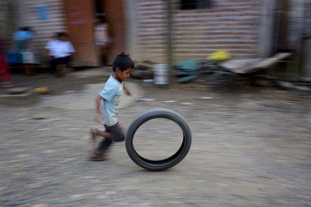 In this Saturday, June 20, 2015 photo, a boy runs while playing with a motorcycle wheel in Samugari, Ayacucho, Peru. (Photo by Rodrigo Abd/AP Photo)