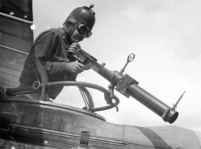 A soldier poses with a Hythe Mk III Gun Camera during training activities at Ellington Field, Houston, Texas in April of 1918. The Mk III, built to match the size, handling, and weight of a Lewis Gun, was used to train aerial gunners, recording a photograph when the trigger was pulled, for later review, when an instructor could coach trainees on better aiming strategies. (Photo by Harry Kidd/WWI Army Signal Corps Photograph Collection via The Atlantic)