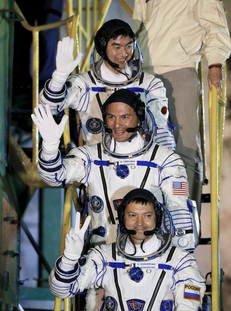 The International Space Station (ISS) crew members Kjell Lindgren of the U.S. (C), Oleg Kononenko of Russia (bottom) and Kimiya Yui of Japan wave as they board the Soyuz TMA-17M spacecraft at the Baikonur cosmodrome, Kazakhstan, July 23, 2015. (Photo by Yuri Kochetkov/Reuters)