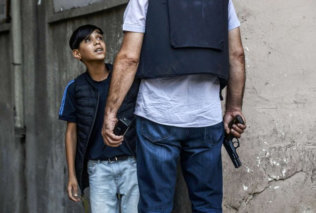 A Turkish police officer asks questions to a young Kurdish boy after an attack against Turkish police officers in the center of Diyarbakir on July 23, 2015. A Turkish police officer was shot dead and a second one wounded today in the mainly Kurdish city of Diyarbakir in the latest in a series of attacks that began with a suicide bombing blamed on ISIL, security sources said. (Photo by Ilyas Akengin/AFP Photo)