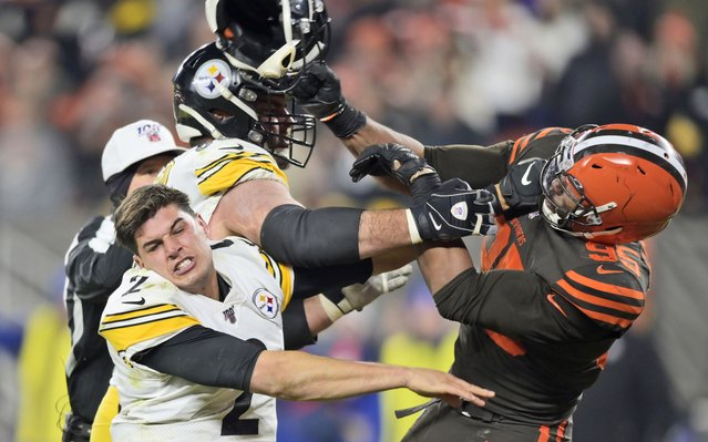 Cleveland Browns defensive end Myles Garrett (95) hits Pittsburgh Steelers quarterback Mason Rudolph (2) with a helmet during the second half of an NFL football game Thursday, November 14, 2019, in Cleveland. (Photo by David Richard/AP Photo)