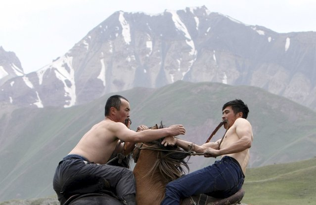 Participants wrestle while riding horses during the Kyrgyz national horse games and festival near the Tulpar-Kul lake in the Chon Alai mountain range, some 3500 metres (11483 feet) above sea level, in the Osh region of Kyrgyzstan, July 25, 2015. (Photo by Vladimir Pirogov/Reuters)