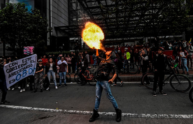 A student spits fire during a protest for Dilan Cruz, a young demonstrator who had been wounded by a member of the Mobile Anti-Disturbance Squadron (ESMAD) during a protest against the Colombian government and died yesterday, in Bogota on November 26, 2019. Under-fire Colombian President Ivan Duque will meet with protest leaders on Tuesday, a minister announced, after five consecutive days of anti-government protests. The meeting will form part of the national dialogue Duque launched on Sunday to address corruption, economic inequality and other woes. (Photo by Juan Barreto/AFP Photo)