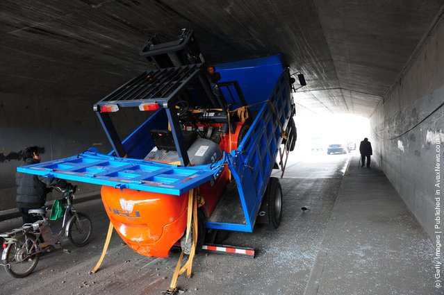 A truck becomes wedged in a tunnel due to carrying a high load at Shi Ba Li Dian Bridge on the East Fourth Ring Road in Beijing, China