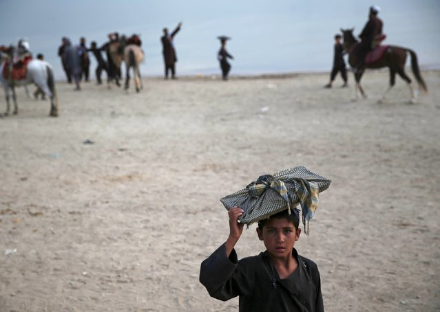 An Afghan boy carries bread on his head for sale along Qargha lake, in Kabul, Afghanistan July 21, 2015. (Photo by Ahmad Masood/Reuters)