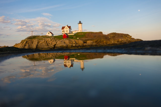 """Nubble in a Puddle"". While in Maine I made a point of visiting several lighthouses. This is Nubble Light – Cape Neddick Lighthouse shot from Sohier Park. The sun was going down behind me so I was about to lose the light. There were several puddles down on the rocks left behind from from high tide so I jumped down, put the camera on the ground and took a shot. Photo location: Cape Neddick Lighthouse, Sohier Park, Maine. (Photo and caption by Christopher V. Sherman/National Geographic Photo Contest)"