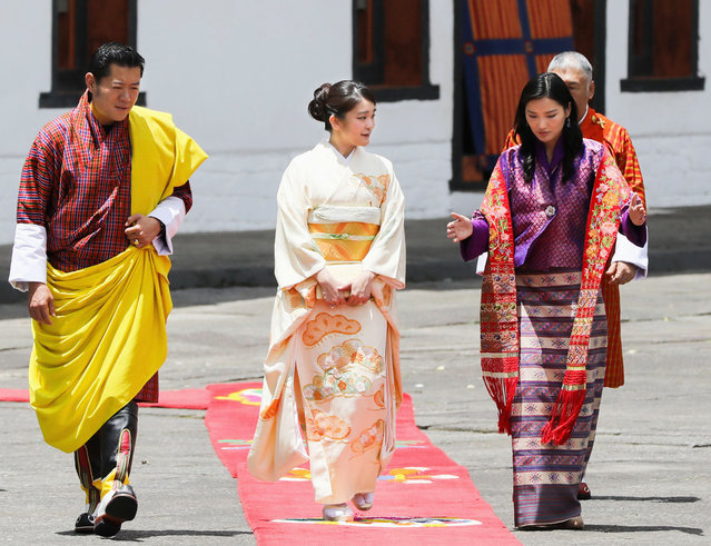 In this Friday, June 2, 2017 photo, Japanese Princess Mako, center, dressed in Japan's traditional kimono, walks with Bhutanese King Jigme Khesar Namgyal Wangchuck, left, and Queen Jetsun Pema at Buddhist monastery and fortress Tashichhodzong in Timphu, Bhutan. Mako, the eldest granddaughter of Japan's Emperor Akihito, who is currently preparing for her engagement, is on a one-week visit to Bhutan. (Photo by Hitoshi Takano/Kyodo News via AP Photo)