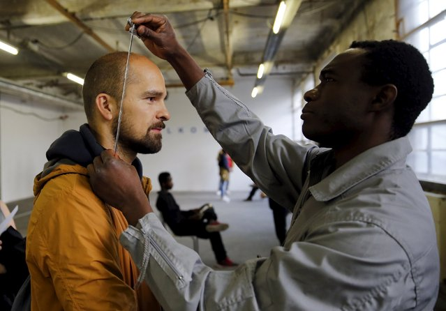 "A migrant welcomes a spectator like in a refugee welcome centre as he performs during the theater project ""Heart of Darkness"", based on a novel by Polish novelist Joseph Conrad at a theater in Berlin, Germany, July 30, 2015. (Photo by Fabrizio Bensch/Reuters)"