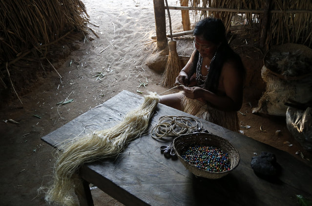A member of the Amazonian Tatuyo tribe works on handicrafts to sell to tourists in her village in the Rio Negro (Black River) near Manaus city, a World Cup host city, June 23, 2014. Because of their proximity to host city Manaus and their warm welcome, the Tatuyo have enjoyed three weeks of brisk business thanks to the World Cup. Usually, they host between 10 and 30 tourists a day. During the World Cup, this number has rocketed to 250 a day, They have become richer and other communities now come to them to sell them juices and fishes. (Photo by Andres Stapff/Reuters)