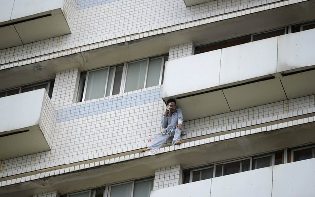 A patient sits outside a hospital building in Changsha, Hunan province, China, on June 25, 2014. Firefighters saved the patient who broke a window on the eighth floor and attempted suicide. The patient was sent to the hospital after a car accident and was confirmed having mental aberrations. (Photo by Reuters/Stringer)