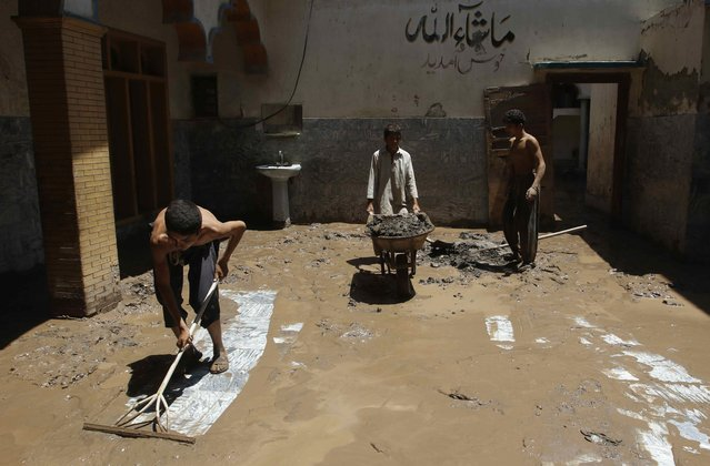 Local residents clear mud from a mosque after heavy rainfall caused flooding in Peshawar, Pakistan, July 27, 2015. (Photo by Khuram Parvez/Reuters)