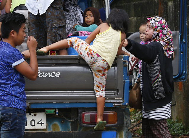 Residents evacuate to safety after a Muslim militant siege in Marawi city, southern Philippines, Thursday, May 25, 2017. Army tanks packed with soldiers rolled into the southern Philippine city Thursday to try to restore control after ISIS-linked militants launched a violent siege that sent thousands of people fleeing for their lives and raised fears of extremists gaining traction in the country. (Photo by Bullit Marquez/AP Photo)