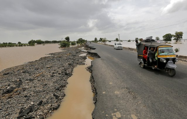 Vehicles move through the damaged national highway after heavy rains on the outskirts of Ahmedabad, India, July 31, 2015. (Photo by Amit Dave/Reuters)