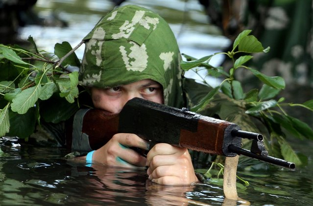 "Wearing Soviet-era fatigues a teenager aims his wooden Kalashnikov chin deep in water as he takes part in a military game simulating special operations at their ""Spetsnaz"" (Special Forces) military adventure training camp near the Belarus village of Talka, some 90 km southeast of the capital Minsk, on July 6, 2014. (Photo by Sergei Gapon/AFP Photo)"