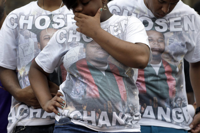"""Supporters of Michael Brown wear shirts with his picture and the message """"Chosen 4 ChangeÆ as they take part in a remembrance ceremony at the spot where he was shot and killed Sunday, August 9, 2015, in Ferguson, Mo. Sunday marks one year since Michael Brown was shot and killed by Ferguson police officer Darren Wilson. (Photo by Jeff Roberson/AP Photo)"""