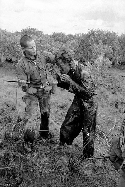 In this Jan. 9, 1964 photo, a South Vietnamese soldier uses the end of a dagger to beat a farmer for allegedly supplying government troops with inaccurate information about the movement of Viet Cong guerrillas in a village west of Saigon, Vietnam