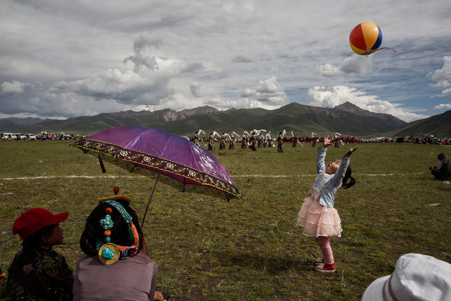 An ethnic Tibetan girl plays as nomads watch traditional dancing on July 25, 2015 at a local government sponsored festival on the Tibetan Plateau in Yushu County, Qinghai, China. (Photo by Kevin Frayer/Getty Images)
