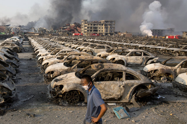 In this photo taken Thursday, August 13, 2015, a man walks past the charred remains of new cars at a parking lot near the site of an explosion at a warehouse in northeastern China's Tianjin municipality. Rescuers have pulled a survivor from an industrial zone about 32 hours after it was devastated by huge blasts in China's Tianjin port. Meanwhile, authorities are moving gingerly forward in dealing with a fire still smoldering amid potentially dangerous chemicals. (Photo by Ng Han Guan/AP Photo)