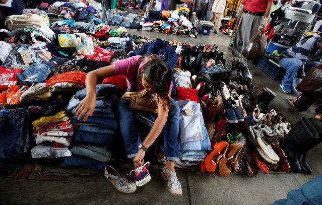A woman tries on shoes at a second-hand market in Caracas, Venezuela, June 26, 2016. (Photo by Mariana Bazo/Reuters)