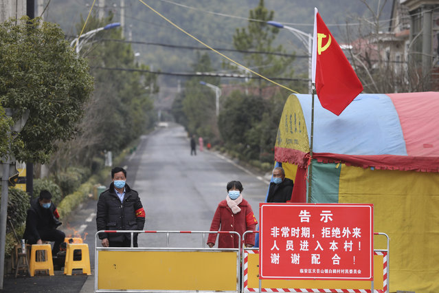 Volunteers stand beneath a Communist Party flag as they man a barricade checkpoint at a village in Hangzhou in eastern China's Zhejiang Province, Monday, February 3, 2020. China sent medical workers and equipment to a newly built hospital, infused cash into financial markets and further restricted people's movement in sweeping new steps Monday to contain a rapidly spreading virus and its escalating impact. (Photo by Chinatopix via AP Photo)
