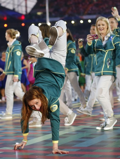 An Australian athlete does a handstand as she arrives with her teammates during the opening ceremony for the Commonwealth Games 2014 in Glasgow, Scotland, Wednesday July 23, 2014. (Photo by Frank Augstein/AP Photo)