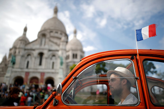 A sightseeing tour Citroen 2CV car is seen parked next to the Sacre Coeur (Sacred Heart) basilica in Paris, France, July 31, 2017. (Photo by Christian Hartmann/Reuters)