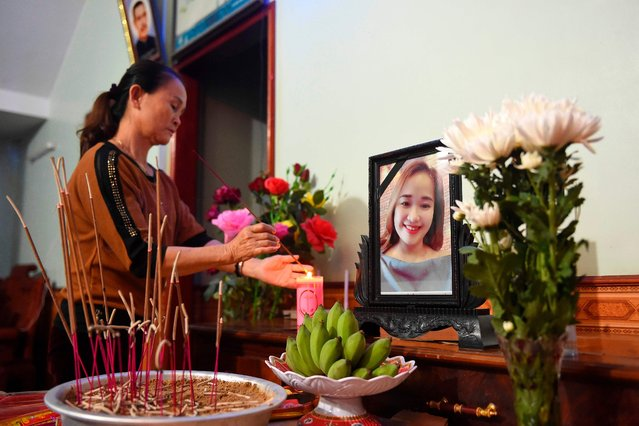A relative lights an incense stick infront of a portrait of Bui Thi Nhung, who is feared to be among the 39 people found dead in a truck in Britain, inside her house in Vietnam's Nghe An province on October 26, 2019. A photo of her missing daughter Bui Thi Nhung, an offering of fruit and a bouquet of flowers – a makeshift shrine laid by a desperate mother in a remote Vietnamese town many fear was home to some of the 39 people found dead in a truck in Britain. More than 20 Vietnamese are feared to be among the bodies found in a refrigerated trailer in an industrial park in Essex east of London on October 23. (Photo by Nhac Nguyen/AFP Photo)