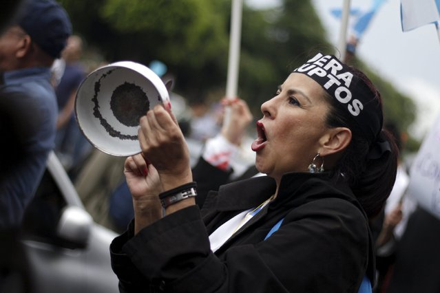 A woman yells as she hits a pan during a protest to demand the resignation of Guatemala's President Otto Perez Molina in Guatemala City, August 15, 2015. Demonstrators are demanding the resignation of Perez Molina for the corruption scandals of politicians close to his government and his administration. (Photo by Josue Decavele/Reuters)