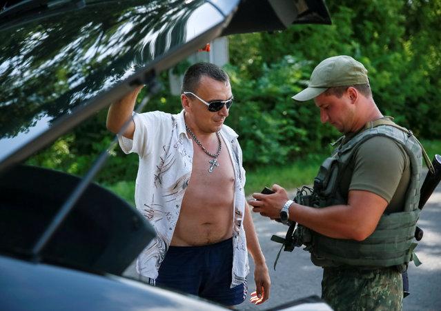 A Ukrainian serviceman checks documents at a checkpoint near Slaviansk, in Donetsk region, Ukraine, June 29, 2016. (Photo by Gleb Garanich/Reuters)