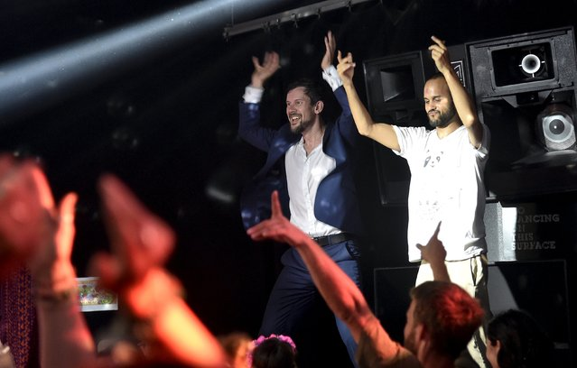 """A club-goer wearing a suit dances at """"Morning Gloryville"""" at the Ministry of Sound in south London August 11, 2015. (Photo by Toby Melville/Reuters)"""