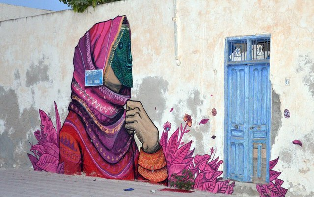 """Graffiti decorates the wall of an old house in the Tunisian island of Djerba on July 29, 2014. More than 100 artists from 40 countries were invited by France-based Tunisian artist Mehdi Ben Cheikh to take part in an initiative to turn Djerba's Erriadh district into an """"open sky museum"""". (Photo by F. Nasri/AFP Photo)"""