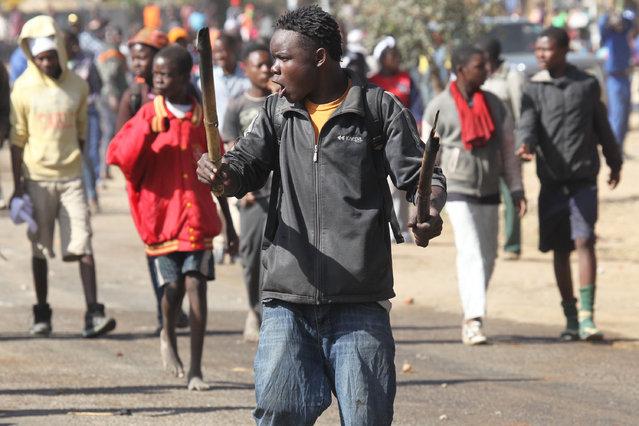 Rioters battle with Zimbabwean police in Harare, Monday, July, 4, 2016. (Photo by Tsvangirayi Mukwazhi/AP Photo)