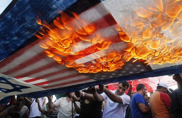 Lebanese and Palestinian protesters set fire to U.S. and Israeli flags during a demonstration to denounce Israeli air strikes on the Gaza strip, in Lebanon's southern port-city of Sidon July 10, 2014. At least 77 Palestinians, most of them civilians, have been killed in Israel's Gaza offensive, Palestinian officials said on Thursday, and militants kept up rocket attacks on Tel Aviv, Jerusalem and other cities in warfare showing no signs of ending soon. (Photo by Ali Hashisho/Reuters)
