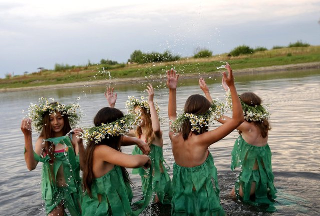A picture made available on 07 July 2016 shows Belarussian girls in mermaids costumes marking the pagan holiday Kupalle on the bank of the Pripyat river in Turov, one of the ancient Belarussian cities located about 270 km from Minsk, Belarus, 06 July 2016. Kupalle, which is the Belarusian version of the midsummer festival during the Summer solstice marking the beginning of Summer, is widely celebrated in Belarus on the night of 06 July. (Photo by Tatyana Zenkovich/EPA)