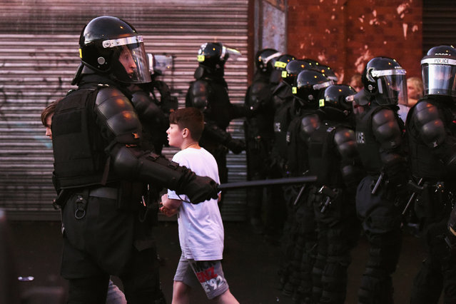 A child is seen walking through Ardoyne area during clashes with police after the annual Twelfth of July Orange Order Parade in Belfast, Northern Ireland, July 12, 2016. (Photo by Clodagh Kilcoyne/Reuters)