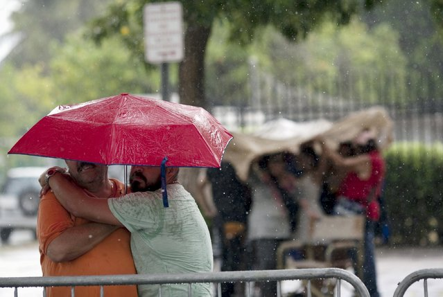 Men embrace under an umbrella while observing same-s*x couples leaving a church after their wedding ceremony in San Juan, Puerto Rico, August 16, 2015. (Photo by Alvin Baez/Reuters)