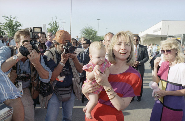 Hillary Rodham Clinton carries 6-month-old Murphy McCollough past news photographers during an impromptu stop in Georgetown, Texas on Thursday, August 27, 1992. The Democratic presidential and vice-presidential candidates and their wives are on a two-day bus tour through Texas. (Photo by Stephan Savoia/AP Photo)