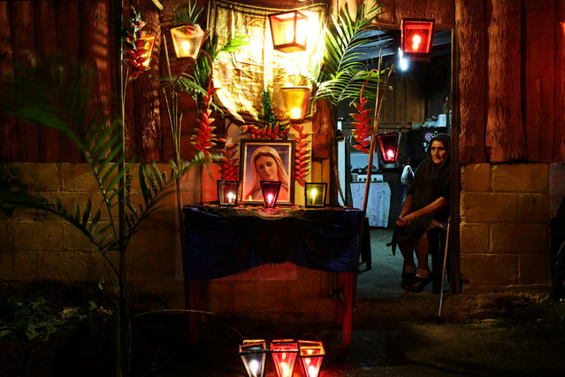 A woman sits outside her house during the Lantern Festival celebrating the eve of the nativity of the Virgin Mary in Apaneca, El Salvador, September 7, 2017. (Photo by Jose Cabezas/Reuters)