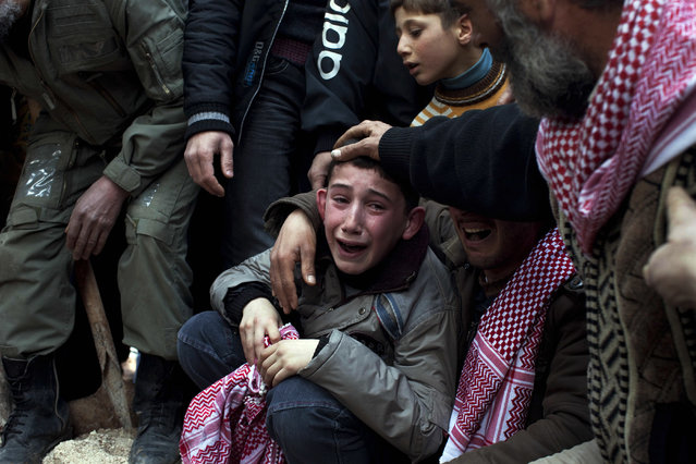 A boy named Ahmed mourns his father, Abdulaziz Abu Ahmed Khrer, who was killed by a Syrian army sniper, during his funeral in Idlib, northern Syria, March 8, 2012. This image was one in a series of 20 by AP photographers that won the 2013 Pulitzer Prize in Breaking News Photography. (Photo by Rodrigo Abd/AP Photo)