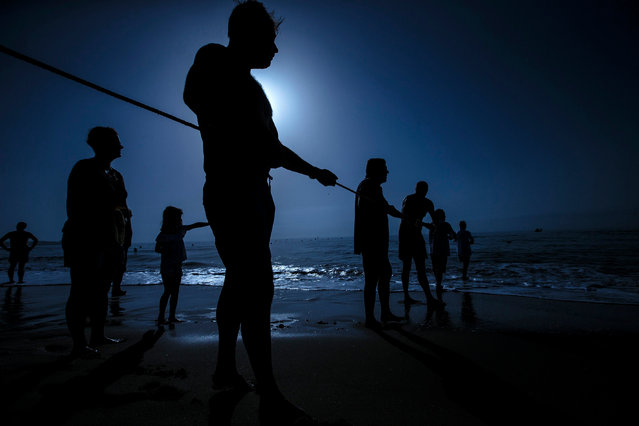 "Fishermen attend the traditional fishing art ""tirada del copo"", nowadays banned, during an event held to evoke the ancient trade of fishing in Los Boliches beach in Fuegirola, Spain, 15 August 2017. This kind of fishing was banned back in the 60s due to secure the fishing resource. (Photo by Jorge Zapata/EPA)"