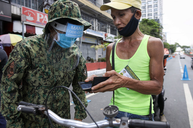 A man is questioned by police at a checkpoint in Manila, Philippines, 01 April 2020. Philippines now has 2,311 coronavirus cases, 96 deaths and 50 recovered. (Photo by Mark R. Cristino/EPA/EFE)