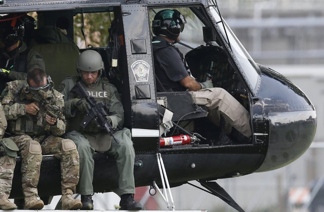Police officers check their weapons before taking off in a helicopter for a manhunt in Fox Lake, Illinois, United States, September 1, 2015. Police with dogs and helicopters are searching woods and swampy areas north of Chicago for three armed suspects after a police officer was shot dead on Tuesday in the suburb of Fox Lake, a local law enforcement official said. (Photo by Jim Young/Reuters)