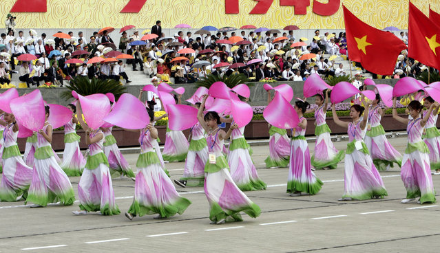 Vietnamese school children perform dances during a military parade in Hanoi, Vietnam, Wednesday, September 2, 2015. The parade was part of events to mark the 70th anniversary of independence from France. Speaking at the parade, President Truong Tan Sang praised the country's achievements over the past 70 years, but warned that corruption is eroding the people's trust in the ruling Communist Party and government. (Photo by Tran Van Minh/AP Photo)