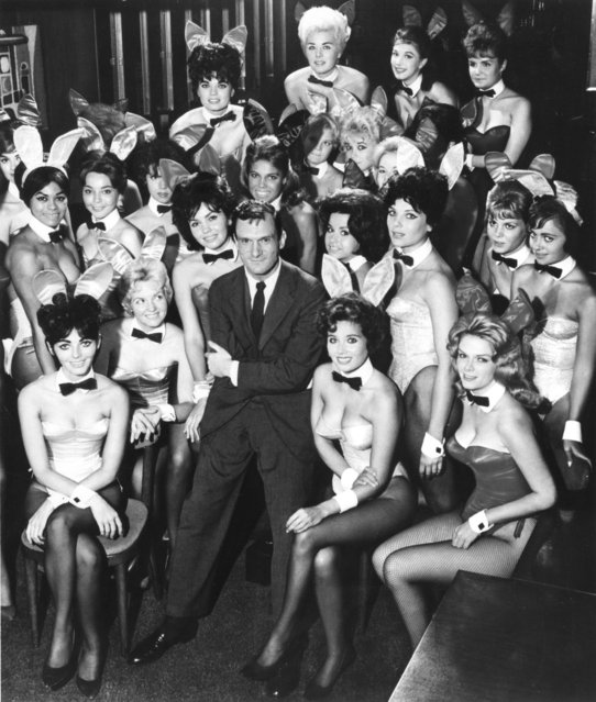 Millionaire publisher of Playboy magazine Hugh Hefner poses with a bevy of bunny girls at one of America's chain of Playboy clubs. (Photo by Helmut Kretz/Getty Images)